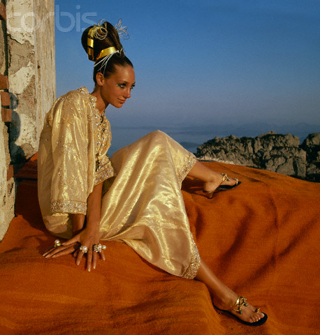 Marisa Berenson intr-un kaftan auriu de Tina Leser, cercei Gripoix si sandale aurii Bernardo, fotografiata de Henry Clarke in 1967